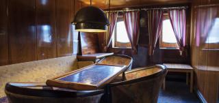 Kuva Boren Cafe Navigaren sisältä. Kuvassa puinen pöytä ja tuoliryhmä.