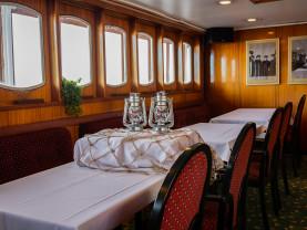 Yksi Boren tarjoilusaleista. Kuvassa pöytiä peräkkäin. Pöydillä valkoiset liinat ja keskellä on koristeena myrskylyhtyjä valkoisen korokkeen päällä. Pöytiä reunustavat puiset tuolit, joissa viininpunaiset kirjaillut pehmusteet selkänojissa.